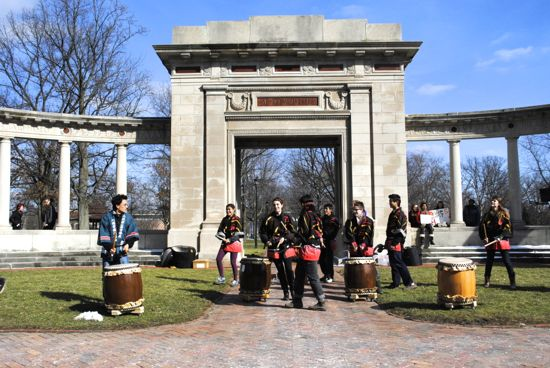 Taiko drummers set up under the memorial arch