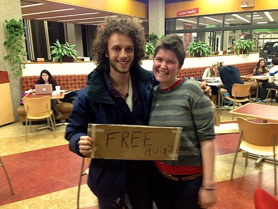 "Two students holding a sign that says ""free hugs"""