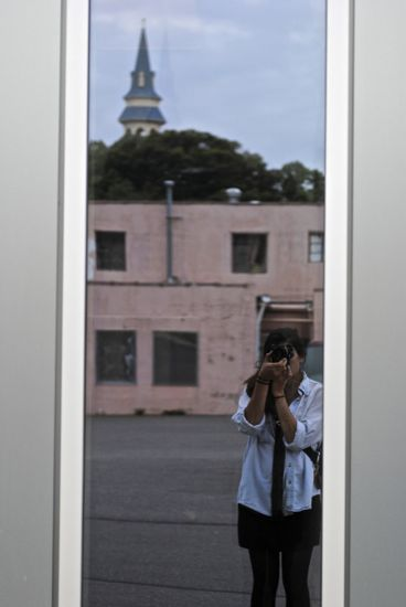 The reflection of a photographer taking a photo against a window