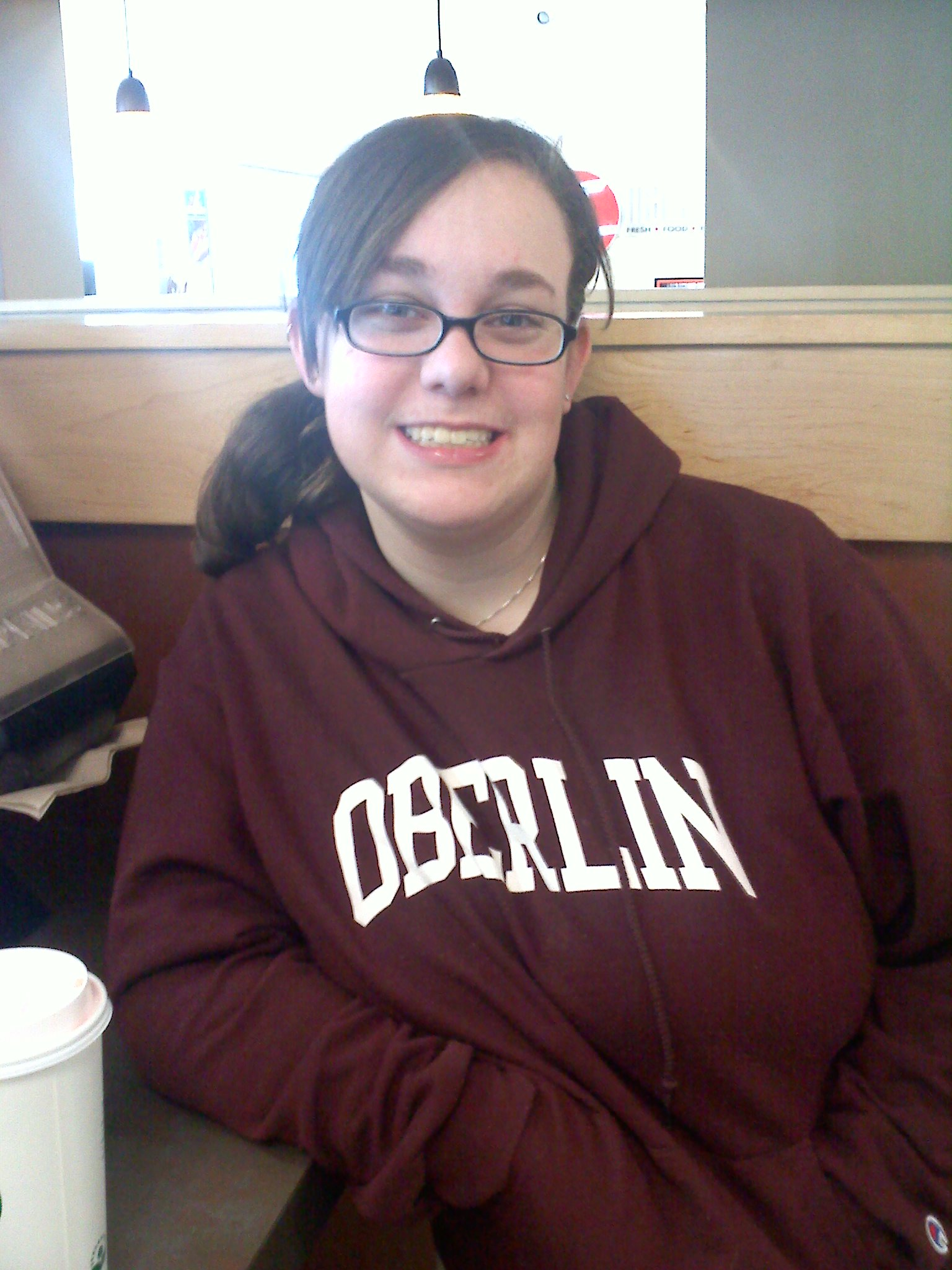 A student poses for a photo wearing an Oberlin sweatshirt