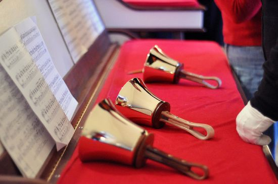 Gold bells lay in front of sheet music on red fabric
