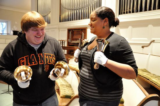 Two musicians smile and hold their bells in front of church pews