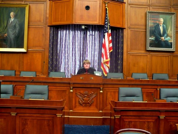 Patrick sits in the chairman's spot at the center of the bench in a stately hearing room