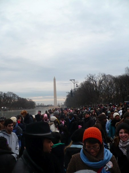 A crowd of people dressed for cold weather. The Washington Monument is in the background.