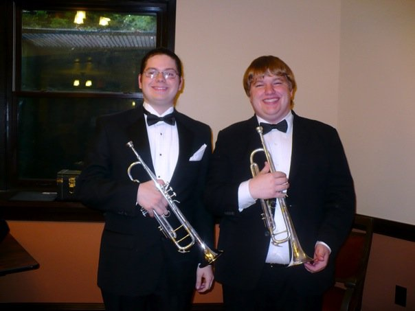 The author posing for a photo with Nick. Both are wearing matching tuxedos and holding trumpets