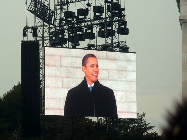 Barack Obama's image is projected on a huge outdoor screen