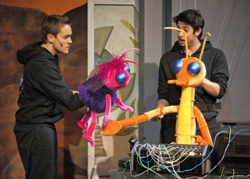 Students on stage acting out bug puppet