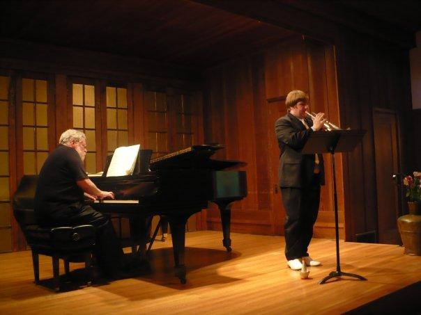 The author playing trumpet on stage wearing a black tuxedo and white dress shoes. An older man is playing the piano behind him