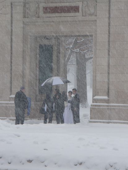 A crowd wearing wedding attire in a snow storm under the arch at Tappan square