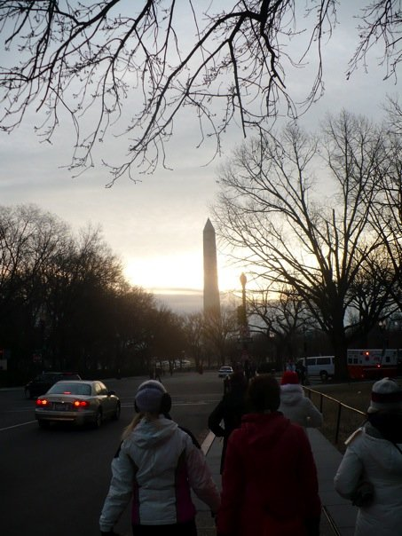 Walking along a busy road, where the sun is rising behind the Washington Monument