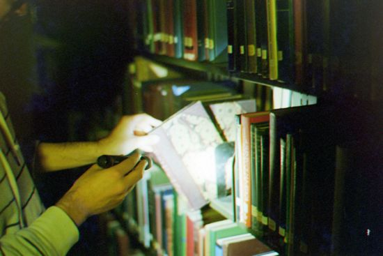 A student pulls a book out of a shelf