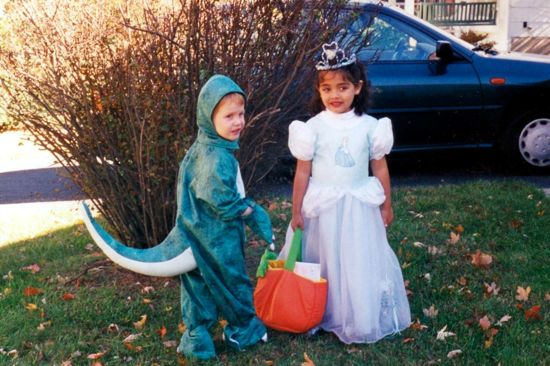 Two children, age 3 or 4, dressed for Halloween. One is a dinosaur and the other is a princess.