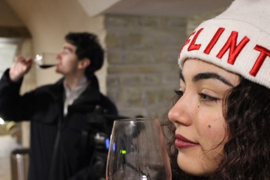 A girl sniffs a glass of wine