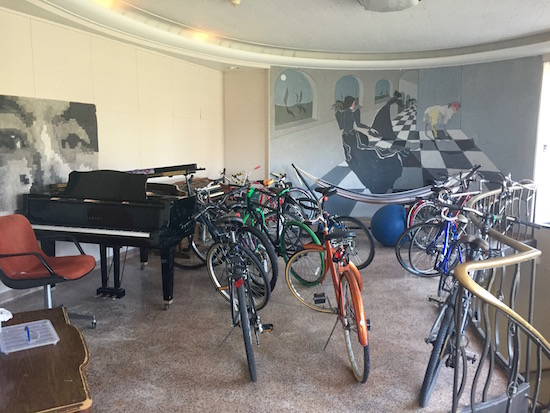 A common area includes a grand piano, several bikes, and a mural.