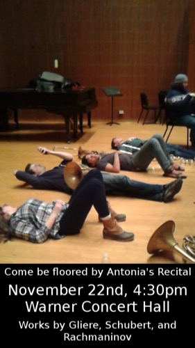 Students laying on the ground holding brass instruments