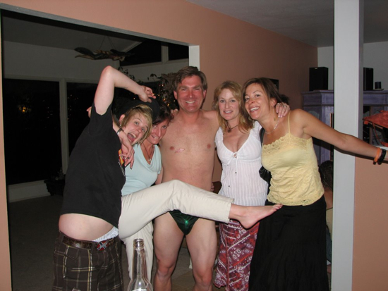 A group of adults pose for a photo. One is wearing only a speedo