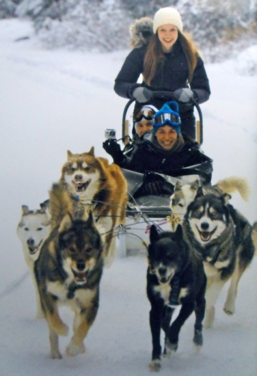 Three people ride on a moving dog sled