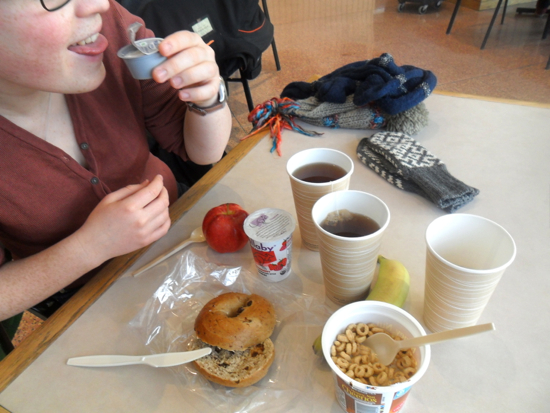 A student sitting at a table with a bagel, cheerios, yogurt, an apple, a banana, and tea