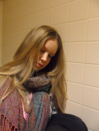 A student in a bathroom stall taking a selfie and pretending to be asleep