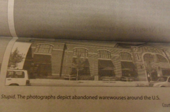 A newspaper photo of a building with the caption: The photographs depict abandoned warewouses around the U.S.