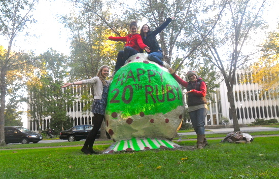 "Students pose in front of a spray painted rock with the words ""Happy 20th Ruby"""