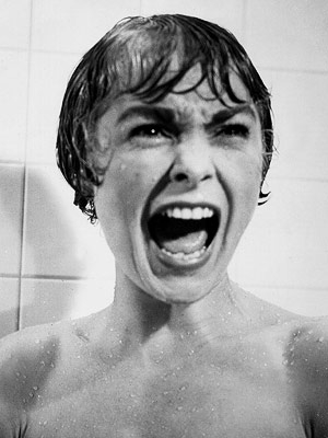A still from a horror film of a woman in a shower screaming