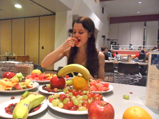 Student eating fruit with plates full of fruit on the table