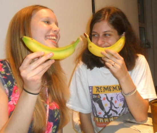 Two students smiling and holding bananas like smiles