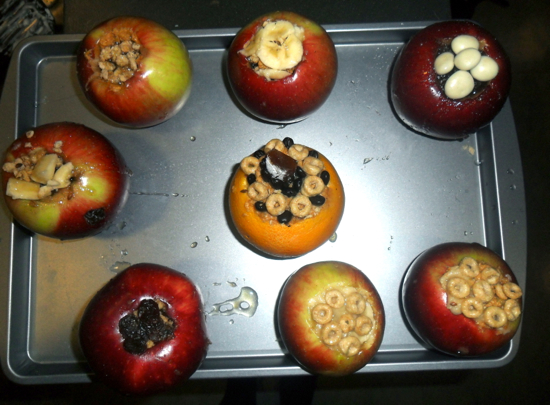 Apples on a baking tray with cereal filling the centers
