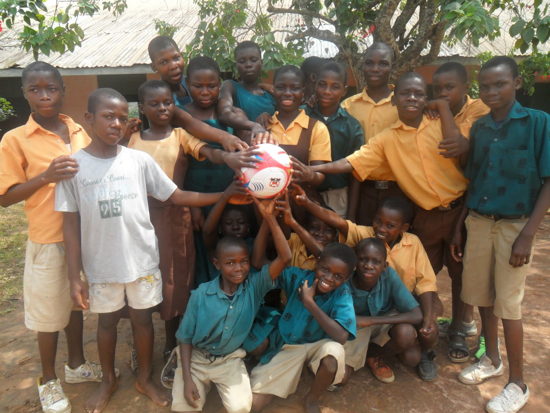 A group of students posing for the photo and touching a soccer ball