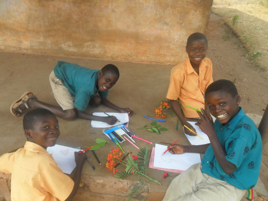 A group of four students coloring flowers