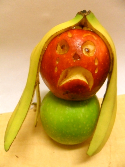 Two apples stacked on top of eachother. The apple on top has a tearful and scared face carved into it. A banana peel hangs over the apple as hair.