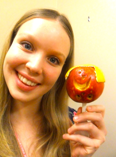 A girl taking a selfie with the upset apple. This time, the apple is upside down and has an orange peel draping over the top.
