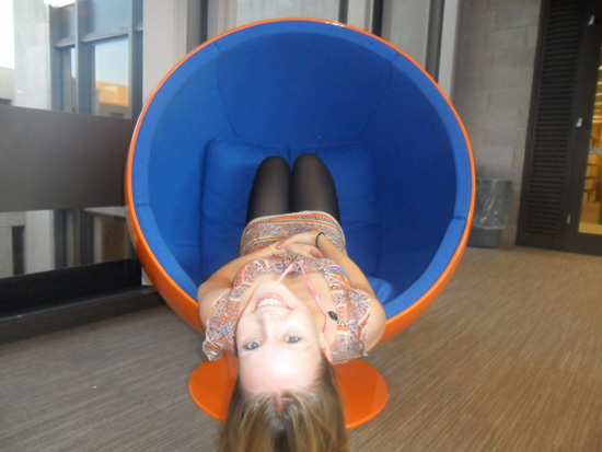 A girl laying in a wombchair backwards, so that her feet are at the head and her head is spilling out of the mouth