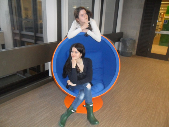 One girl sitting in a wombchair, contemplating with her fist raised to her chin. Another girl stands behind the wombchair with her arms resting over the top, pointing at something out of sight