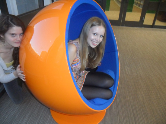 One girl sitting in the wombchair and peeking out to smile at the camera. Another girl can be seen kneeling behind the wombchair with her hands on the back of it