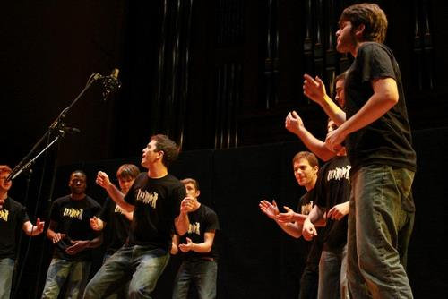 A group of students singing and performing on stage