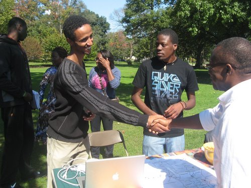 A student, standing behind a table, shakes the hand of an adult