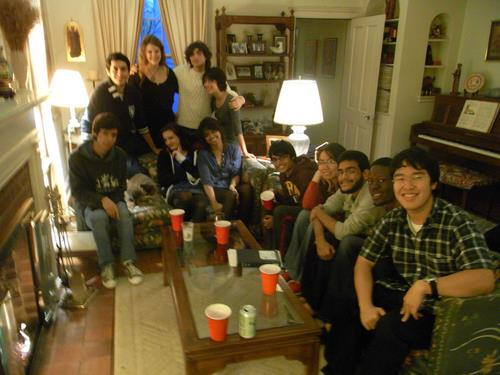 A group of students in a living room smiling for a picture