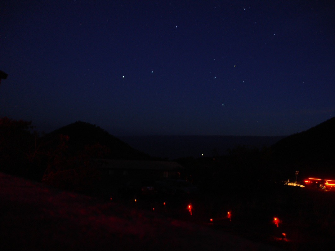 Starry sky above silhouetted mountains and the sea