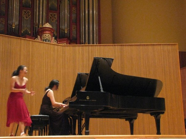 On stage, Juliette plays piano while Sophia looks a bit frantic.