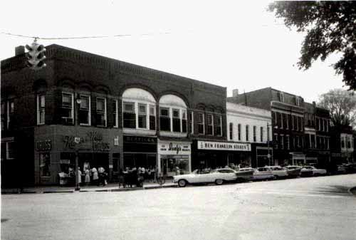 A black and white picture of the SW corner of College and Professor st. A drug store is on the corner and Herricks jewelry sits to its right.