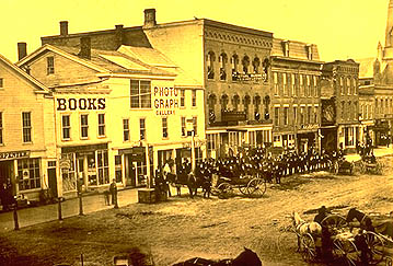 A yellow-tinted photo of the corner of College and Main st. Horses and buggies sit outside of the shops