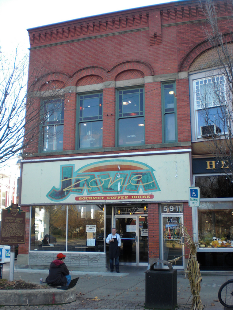 "The sign of the store front on the SW corner of College and Main st. The store sign says ""Java Zone; Gourmet Coffee House."" A man with an apron stands outside the door."