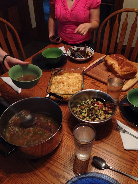 On a table: a pot of soup, loaf of fresh bread, bowl of bean salad, and pan of mac and cheese.