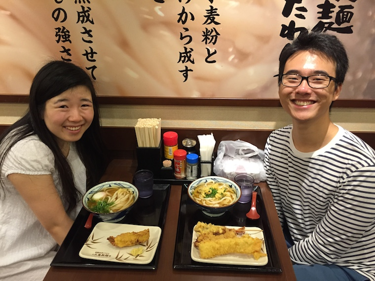 Two people smiling and posing for the photo with trays of noodle soup in front of them