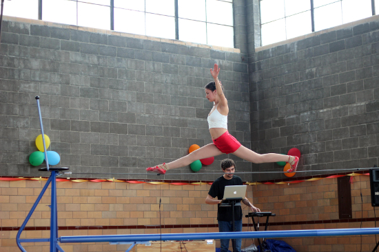 A beam walker jumps improbably high above the beam.