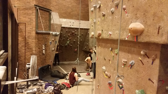 Several angled climbing walls surround climbers on the ground and on the walls