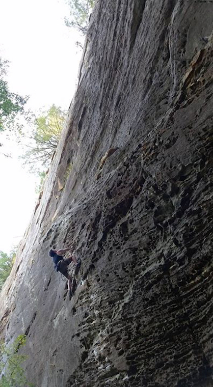 A climber ascending a very steep natural wall