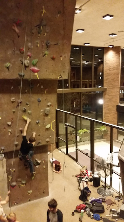 A climber, harnessed, ascends a wall as other onlook